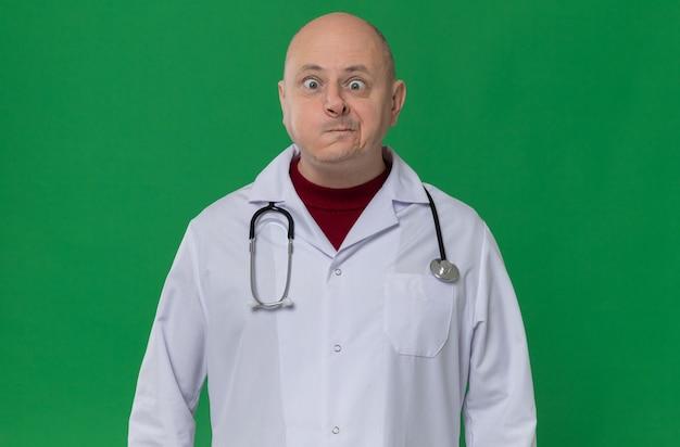 Lustiger erwachsener mann in arztuniform mit stethoskop, das die augen zusammenkneift