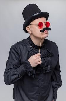 Lustiger erwachsener mann mit zylinder und sonnenbrille in schwarzem gothic-hemd, der einen falschen schnurrbart am stock hält und zur seite schaut