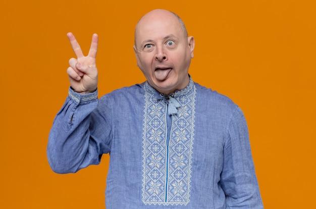 Lustiger erwachsener slawischer mann im blauen hemd streckt seine zunge heraus und gestikuliert siegeszeichen