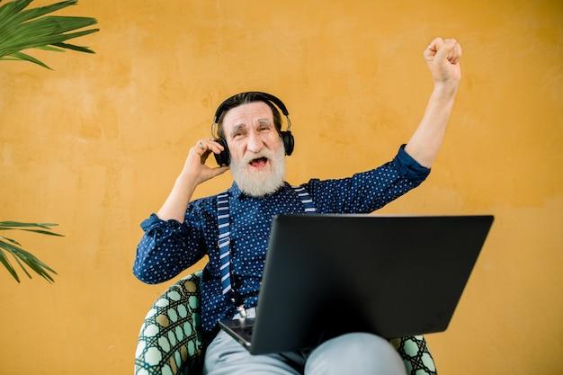 Lustiger freudiger bärtiger mann mit kopfhörern, die im stuhl auf gelbem wandhintergrund sitzen und laptop-computer verwenden