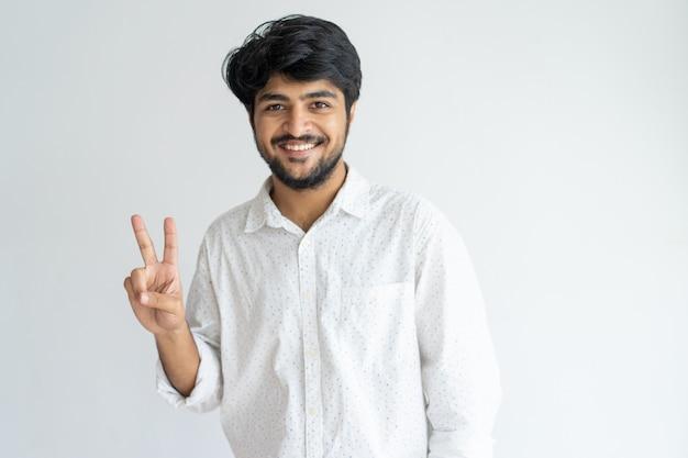 Lustiger freundlicher junger indischer mann, der friedenszeichen zeigt und kamera betrachtet.