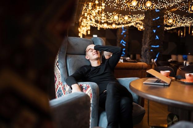 Lustiger fröhlicher junger mann in einem stilvollen schwarzen hemd in trendigen jeans sitzt an einem vintage-holztisch auf einem stuhl in einem café