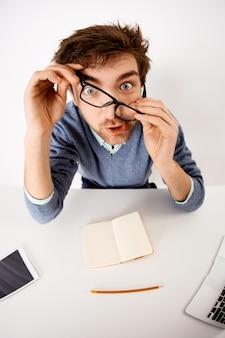 Lustiger gelangweilter kerl mit unordentlichem haar, bart, sitzen schreibtisch, der mit brillengläsern spielt, verrückt starrt, zögern bei der arbeit