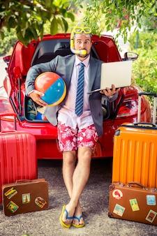 Lustiger geschäftsmann bereit zu stolpern mann steht in der nähe von rotem auto sommerferien und reisekonzept travel