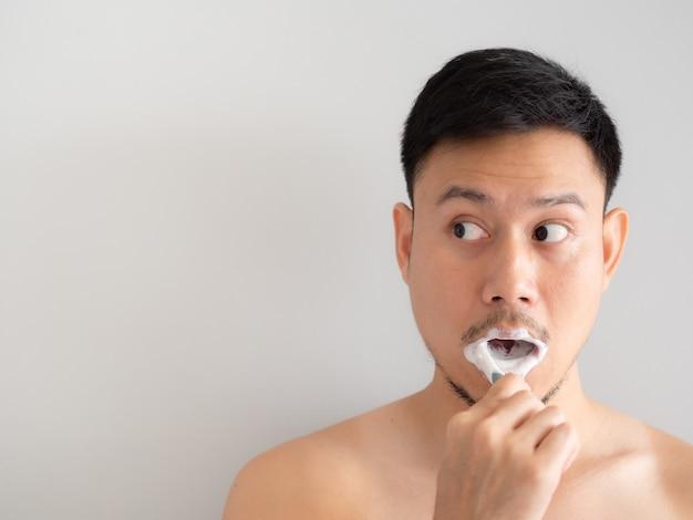 Lustiger gesichtsmann putzt seine zähne mit schaum über seinem gesicht.
