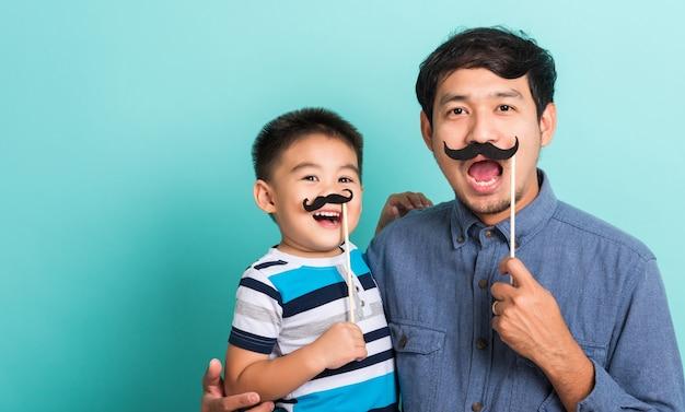 Lustiger glücklicher hipster-vater der familie und sein sohnkind, die schwarze schnurrbartstützen für das nahe gesicht der fotokabine halten