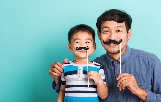 Lustiger glücklicher hipster-vater der familie und sein sohnkind, die schwarzen schnurrbart nahes gesicht halten