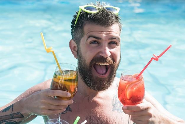Lustiger glücklicher mann, der schwimmt und cocktail an der poolbar trinkt.