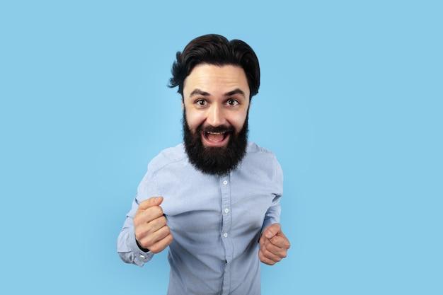 Lustiger glücklicher mann über blauem raum Premium Fotos