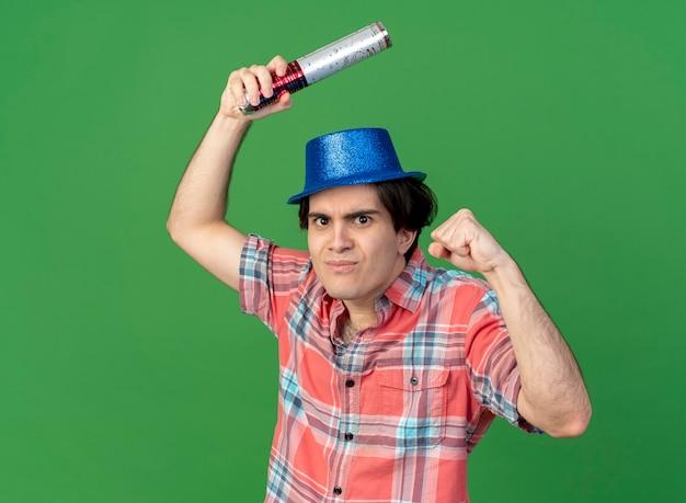 Lustiger gutaussehender kaukasischer mann mit blauem partyhut hält konfettikanone und hält faust