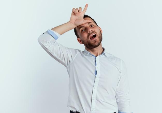 Lustiger gutaussehender mann legt hand auf stirn gestikulierendes verliererzeichen lokalisiert auf weißer wand