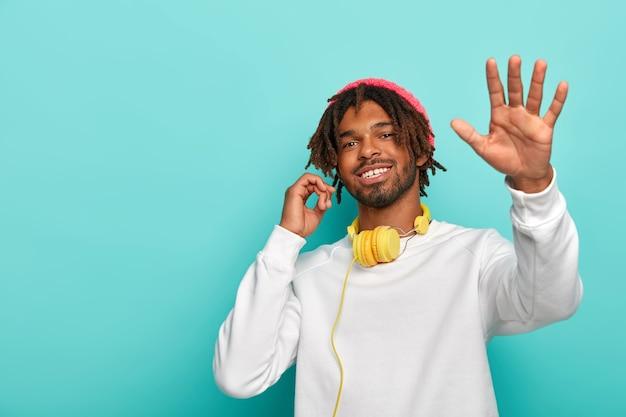 Lustiger hipster-mann tanzt, verwendet stereokopfhörer, isoliert über blauem hintergrund, kopierraum.