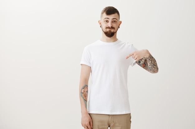 Lustiger hipster-student mit tätowierungen, die finger nach unten zeigen und dumm schmollen