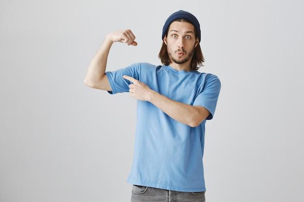 Lustiger hipster-typ im blauen t-shirt und im beanie-flex-bizeps, der starken muskel zeigt