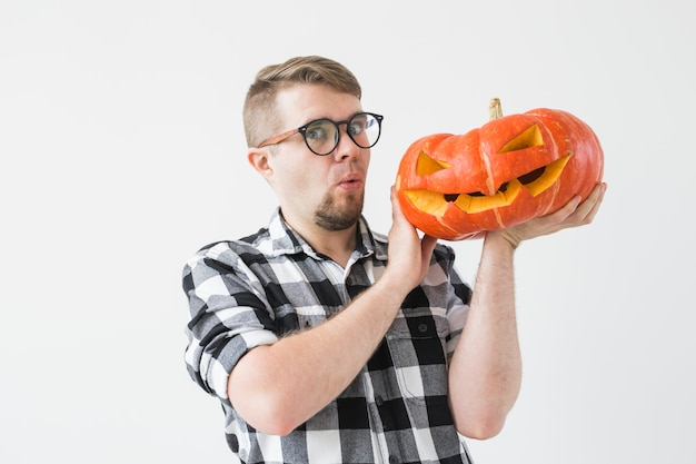 Lustiger hübscher bärtiger mann mit geschnitztem halloween-kürbis