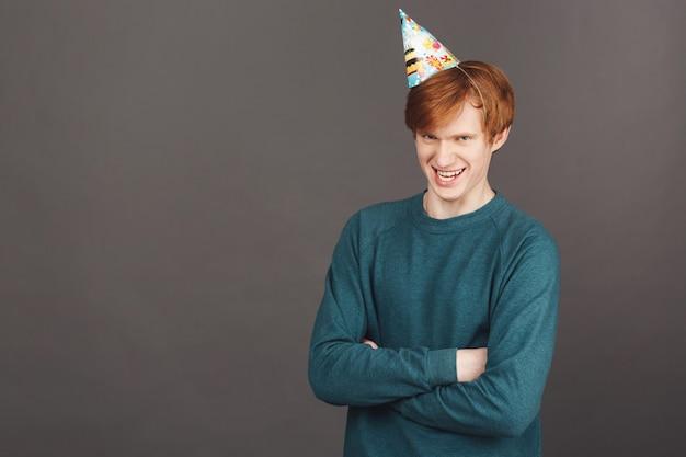 Lustiger hübscher junger rothaariger männlicher student im stilvollen grünen sweatshirt und im partyhut, die hände mit albernem ausdruck kreuzen