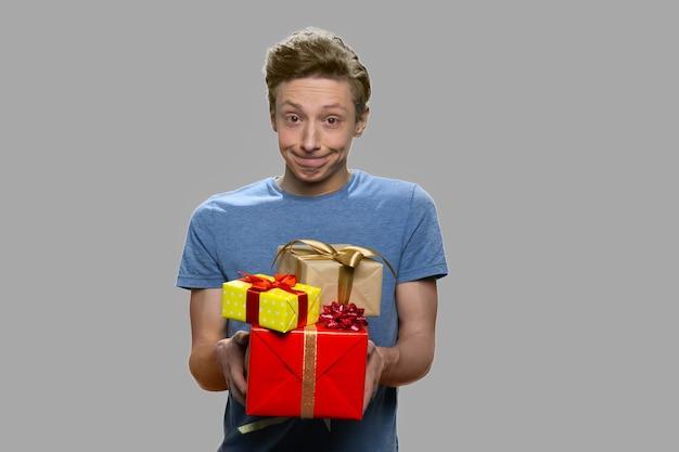 Lustiger jugendlich junge, der geschenkboxen anbietet. teenager-typ, der geschenkboxen gegen grauen hintergrund hält. frohes urlaubskonzept.