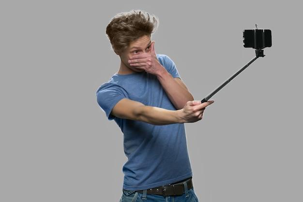 Lustiger jugendlich junge, der selfie mit selfie stock nimmt. junge, der einbeinstativ steht gegen grauen hintergrund. jugend-, technologie- und spaßkonzept.