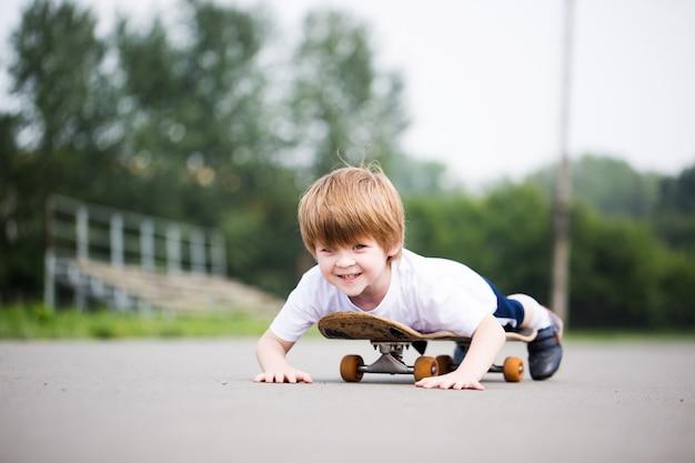 Lustiger junge auf einem skateboard. kid riding skate im freien.