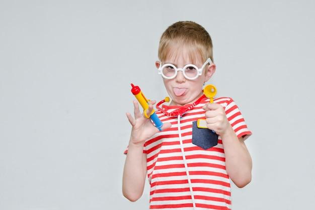 Lustiger junge, der doktor spielt. spielzeugspritze, brille und phonendoskop. porträt