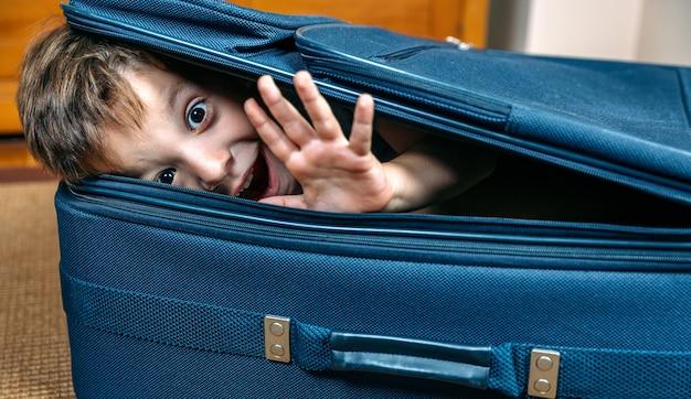 Lustiger junge, der in einem koffer lächelt, der bereit ist, in den urlaub zu fahren