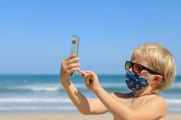 Lustiger junge, der selfie foto durch smartphone am tropischen meeresstrand nimmt.