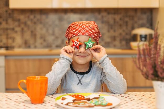 Lustiger junge, der spaß zu hause hat, hält kekse sterne