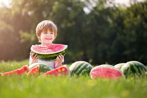 Lustiger junge. glückliches lächelndes kind, das wassermelone draußen im frühlingspark isst.