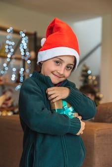 Lustiger junge im weihnachtshut mit präsentkarton