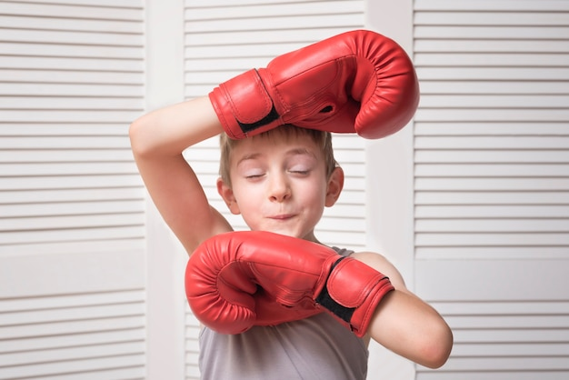 Lustiger junge in den roten boxhandschuhen. sportkonzept