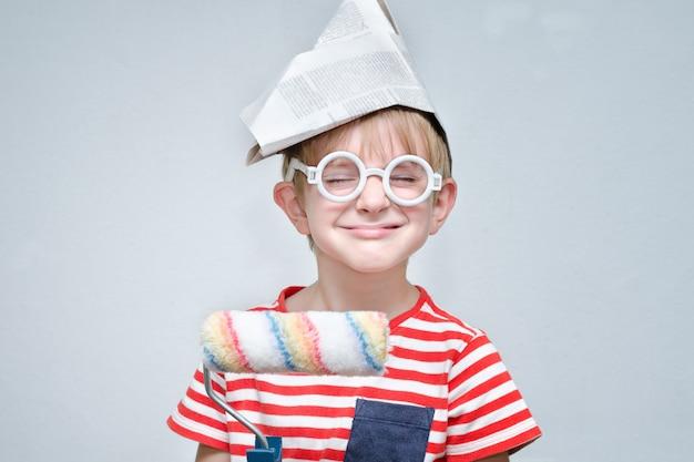 Lustiger junge in einem papierhut mit einer rolle in seinen händen.
