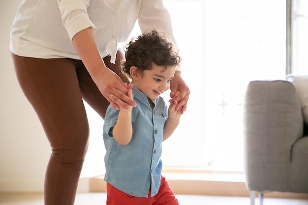 Lustiger junge mit gemischten rennen, der lernt, mit hilfe der mutter zu gehen, nach unten zu schauen und zu lächeln. beschnittene mutter, die sohnhände hält und kleinkind im blauen hemd hilft. familienzeit, kindheit und konzept des ersten schrittes