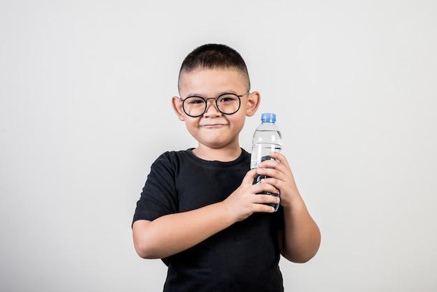 Lustiger junge mit wasserflasche in der atelieraufnahme