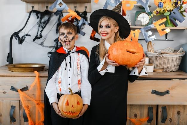 Lustiger junge und mädchen, die halloween-kostüme tragen, die kürbisse auf halloween-landschaftshintergrund halten. hochwertiges foto