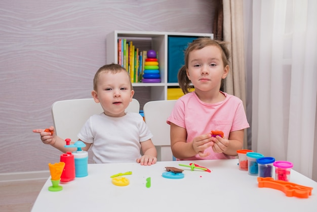 Lustiger junge und mädchen spielen play-doh am tisch im kinderzimmer