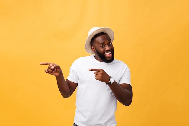 Lustiger junger afrikanischer kunde, der glücklich lächelt und seine zeigefinger auf kamera zeigt, als ob sie sie wählen und zu großem verkauf einladen.
