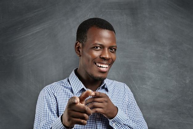 Lustiger junger afrikanischer kunde, der glücklich lächelt und seine zeigefinger zeigt, als ob er sie wählt und zum großen verkauf einlädt. positive emotionen, mimik, gefühle. selektiver fokus