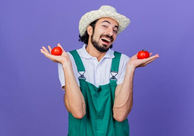 Lustiger junger bärtiger gärtnermann, der overall und hut hält und frische tomaten hält, die fröhlich über der blauen wand stehen