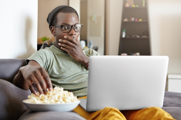 Lustiger junger dunkelhäutiger mann, der auf grauem sofa im wohnzimmer mit notizbuch-pc auf seinem schoß sitzt, mit geschocktem oder verängstigtem blick auf bildschirm schauend, mund mit der hand bedeckend, während er gruseligen film sieht