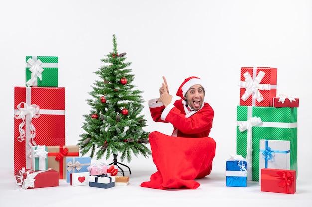 Lustiger junger erwachsener verkleidet als weihnachtsmann mit geschenken und verziertem weihnachtsbaum, der auf dem boden sitzt, der oben auf weißem hintergrund zeigt