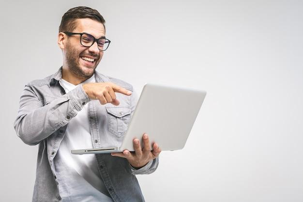 Lustiger junger hübscher mann im hemd, der laptop hält und lächelt, während er gegen weißen hintergrund steht. habe spaß.
