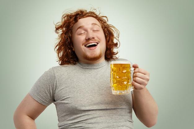 Lustiger junger kaukasischer mann, der sich glücklich und entspannt fühlt und frisches kaltes bier in seinen händen nach hartem arbeitstag vorwegnimmt und augen im genuss schließt. bärtiger übergewichtiger rothaariger mann, der lager trinkt