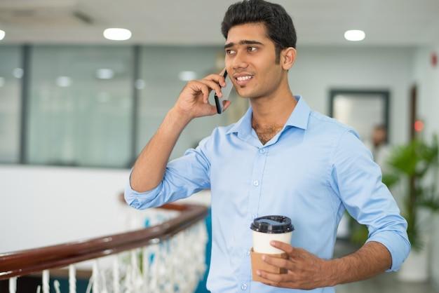 Lustiger junger männlicher manager, der am telefon spricht und kaffee trinkt
