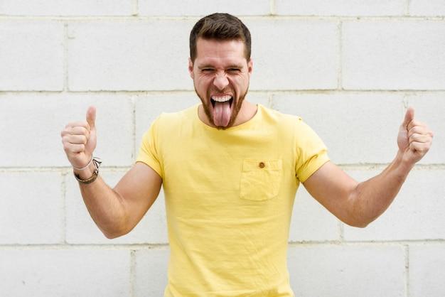 Lustiger junger mann auf backsteinmauer mit dem lustigen ausdruck, der heraus zunge haftet.