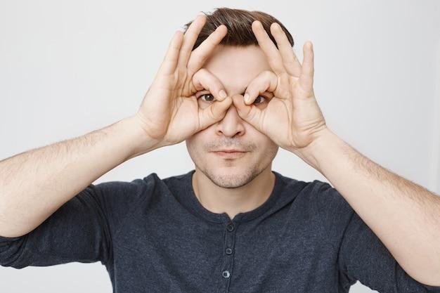 Lustiger junger mann, der falsche brille mit seinen händen macht