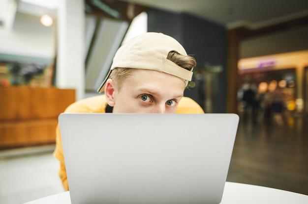 Lustiger junger mann, der sich hinter einem laptop versteckt und mit einem auge späht