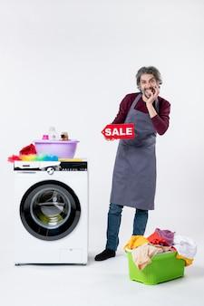 Lustiger junger mann der vorderansicht, der das verkaufsschild in der nähe des wäschekorbs der waschmaschine auf weißem hintergrund hält