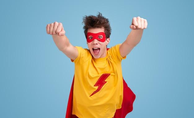 Lustiger junger mann im superheldenumhang und im maskenöffnungsmund und in den geballten fäusten beim fliegen in richtung kamera gegen blauen hintergrund