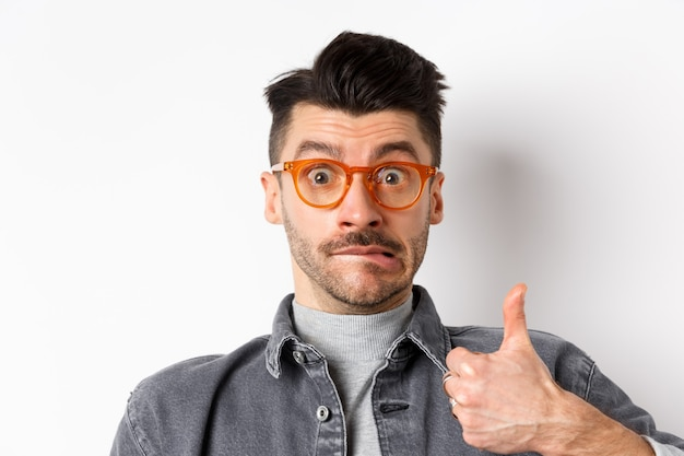 Lustiger junger mann in den gläsern zeigen daumen oben, beißende lippe und sehen unentschlossen aus, auf weißem hintergrund stehend.