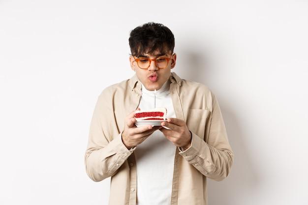 Lustiger junger mann in gläsern, die kerze blasen und wunsch auf geburtstagstorte machen, fröhlich gegen weiße wand stehend.
